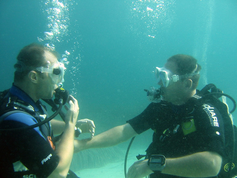 men checking diving gear