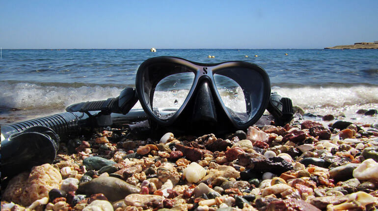scuba mask on the sea shore